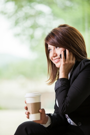 Beautiful young Hispanic business woman talking on her cell phone while drinking some coffee photo