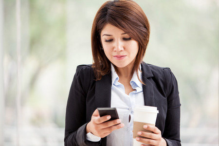 Beautiful business woman reading some emails on her cell phone while taking a coffee break photo
