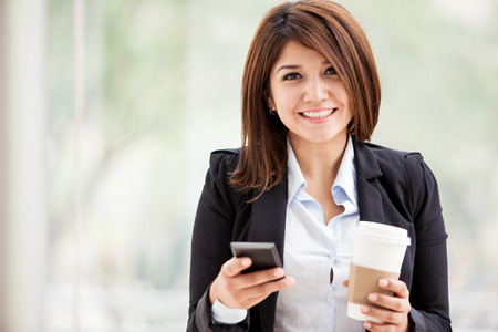 Gorgeous young businesswoman social networking on her cell phone during a coffee break photo