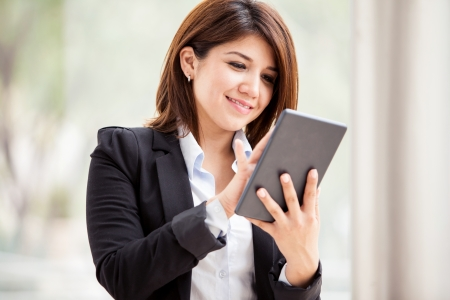 Cute business school student using a tablet to do some social networking and smiling photo