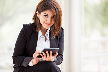 Portrait of a cute business girl using a tablet computer and smiling photo
