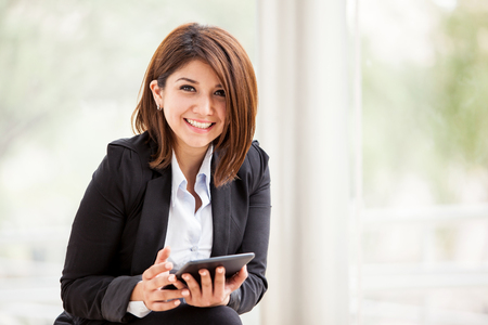 Pretty brunette on a suit working social networking on a tablet computer and smiling photo