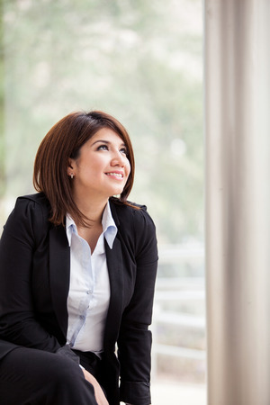 people looking up: Portrait of a beautiful young business woman looking up towards copy space Stock Photo