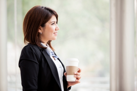 woman profile: Beautiful young brunette wearing a suit and taking a coffee break from work Stock Photo