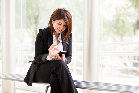 Cute and happy businesswoman sending a text to a friend with her cell phone photo