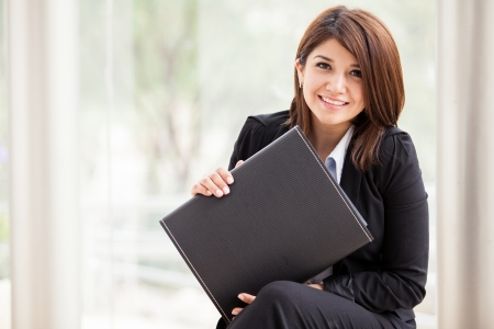 Portrait of a young Hispanic female business school student holding a briefcase and smiling