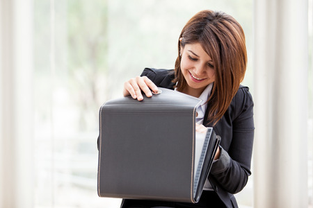 Pretty Latin businesswoman looking for some important documents on a briefcase photo