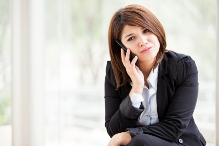 Young Latin business woman taking a very serious phone call from work Stock Photo