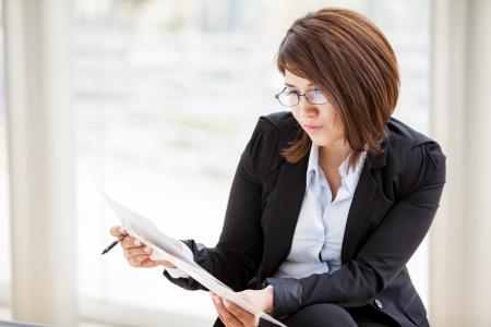 revisando documentos: Empresaria linda con gafas y se enfocaron revisar algunos trabajos