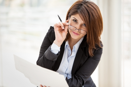 Cute and sexy businesswoman wearing glasses and looking straight to the camera while doing some work photo
