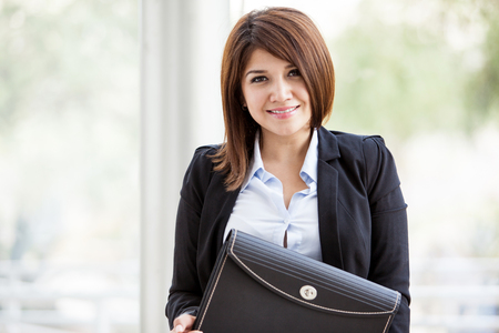Portrait of a cute female architect wearing a suit and carrying a briefcase while smiling photo