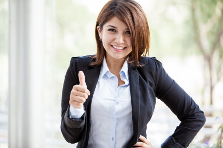 Happy Hispanic business woman on a suit giving a thumb up in a sign of approval photo