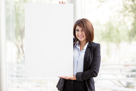 advertise: Happy young business woman holding a big white sign to advertise your latest product or deal