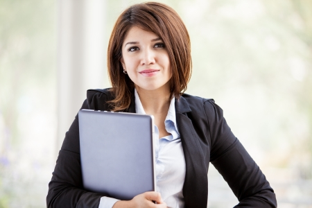 sales executive: Portrait of a beautiful Hispanic - Asian business school student carrying a laptop computer Stock Photo