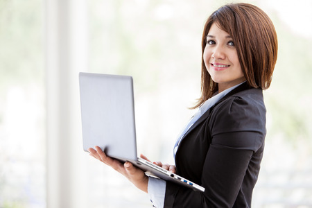 asian architect: Cute young Hispanic business woman working on a laptop computer and smiling Stock Photo