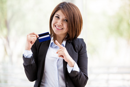 Gorgeous female Asian bank representative holding a credit card in one hand and pointing at it with the other