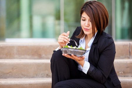 Beautiful business woman eating a healthy salad and taking a break from work photo