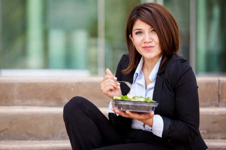 legal office: Cute business woman eating a healthy salad and relaxing outdoors