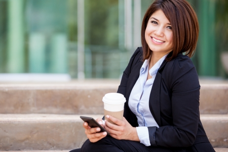 business woman phone: Happy Hispanic business woman sending a text message on her cell phone and drinking some coffee