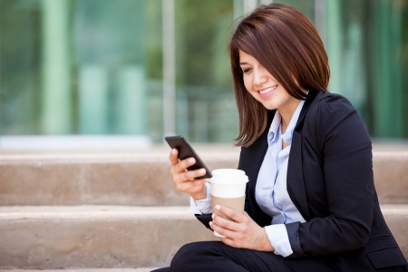 Happy young woman in a suit social networking on her cell phone and drinking coffee photo
