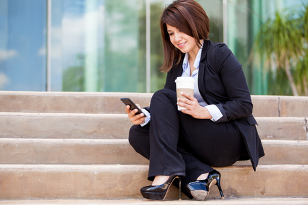 Cute young businesswoman taking a coffee break and sending a text message on her cell phone photo