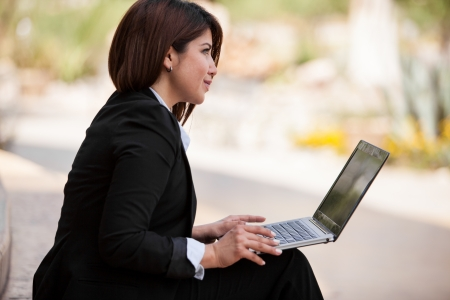 Pretty businesswoman doing some work on her laptop computer outdoors on a sunny day Stock Photo - 22281976