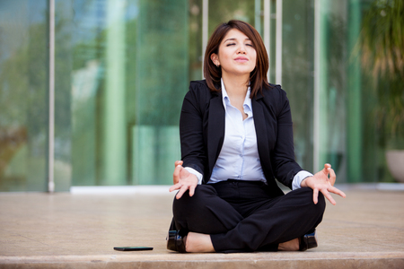 Beautiful Hispanic businesswoman relaxing and meditating outdoors by doing some yoga