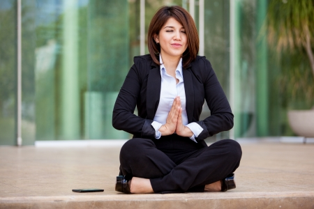 Cute young businesswoman doing some yoga and clearing her mind at work photo