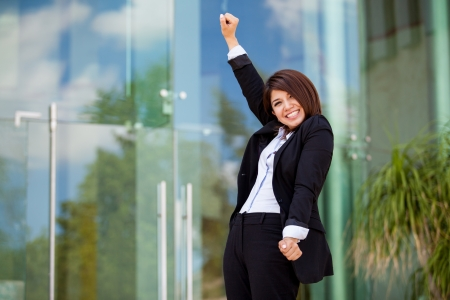 sales person: Happy female business school student raising her arms and celebrating her success