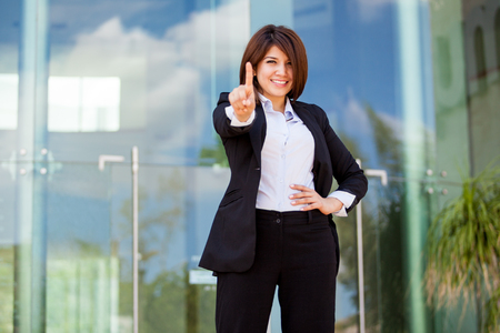 numero uno: Hermosa empresaria hispana señalando que su empresa es la número uno con el dedo