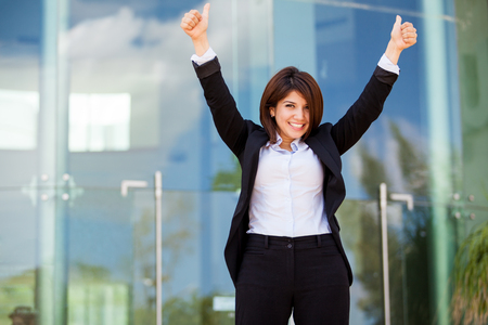 Happy and successful businesswoman raising her arms and celebrating photo
