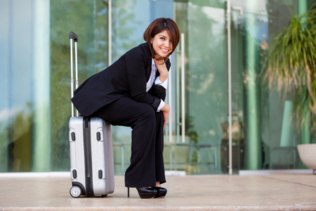 Cute young businesswoman sitting on her suitcase and waiting for her flight photo