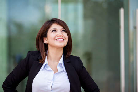 Cute Hispanic - Asian businesswoman smiling and looking up towards copy space photo