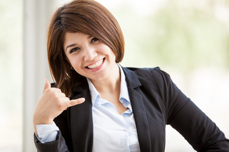 Gorgeous Hispanic business woman asking for you to call using a hand sign