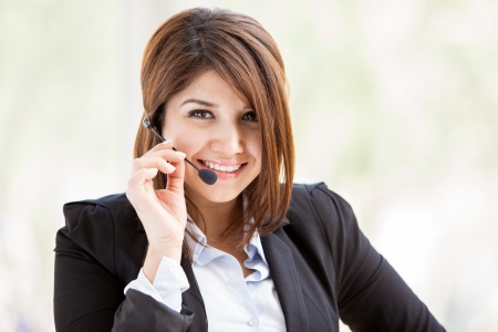 contact center: Happy Hispanic female call center representative wearing a suit and a headset and taking a customer service call Stock Photo