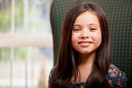 Portrait of a pretty little girl relaxing in the living room and smiling Stock Photo - 22763913