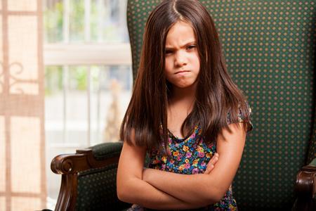 Weinig Spaans meisje met gekruiste armen en echt boos over iets