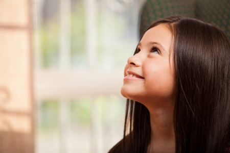 Gorgeous little girl smiling and looking up towards copy space Stock Photo - 22763927