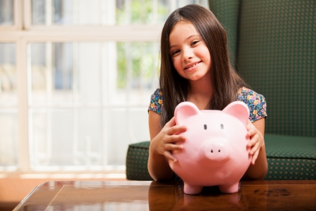 Pretty little girl holding her piggy bank and smiling in the living room Stock Photo - 22763928
