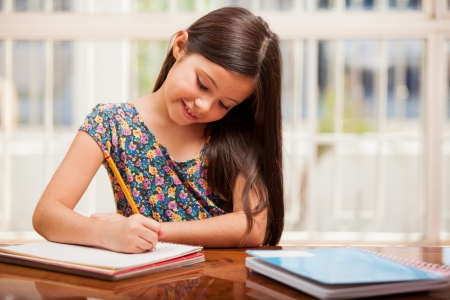 learning by doing: Pretty little girl enjoys learning and doing some homework