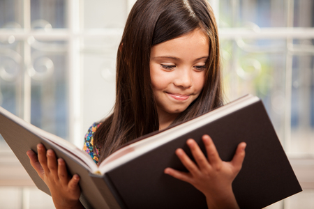 child reading: Cute little Hispanic girl reading a story from a big book in the living room Stock Photo