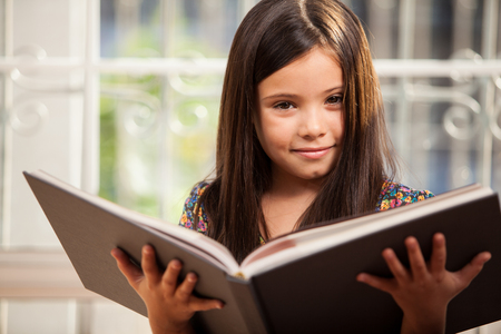 one story: Little Hispanic girl relaxing and reading a storybook at home