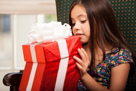 Cute little girl peeking inside of a gift box Stock Photo - 22568595