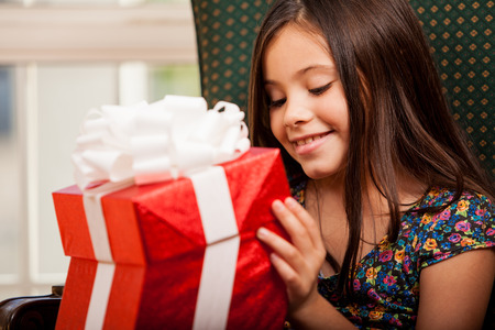 Excited little brunette opening a gift box and smiling Stock Photo - 22568592