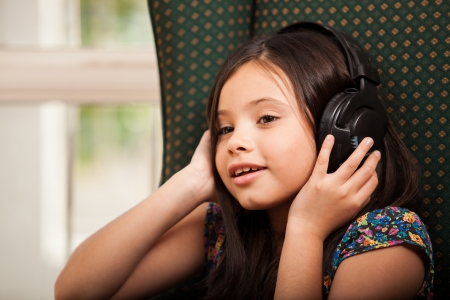 Pretty little Hispanic girl wearing headphones and listening to music photo