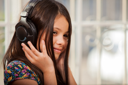 Beautiful kid wearing headphones and listening to some music at home Stock Photo - 22568599