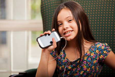 Happy little Latin girl listening to music on her cell phone and showing the screen  photo