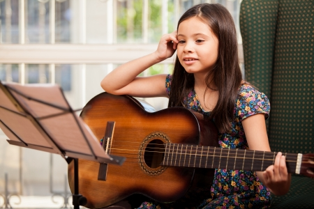 sheet music: Cute little girl practicing her guitar lessons at home