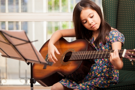 instrument: Pretty little girl practicing some new sound on a guitar at home Stock Photo