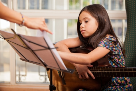 sheet music: Cute little girl playing the guitar during one of her guitar lessons at home